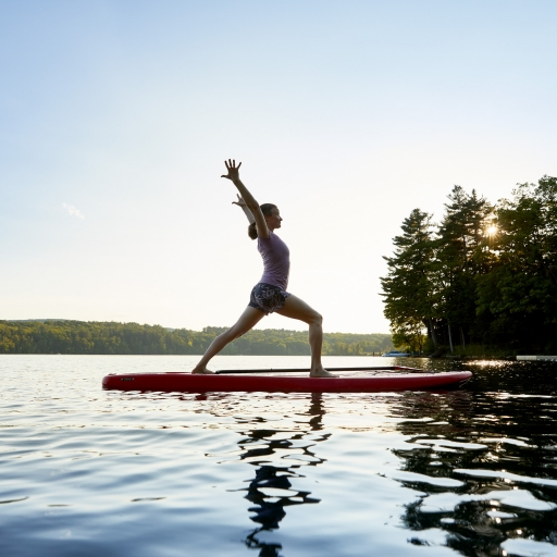 Guest enjoying paddleboard Yoga at our wellness resort in Lenox, Ma